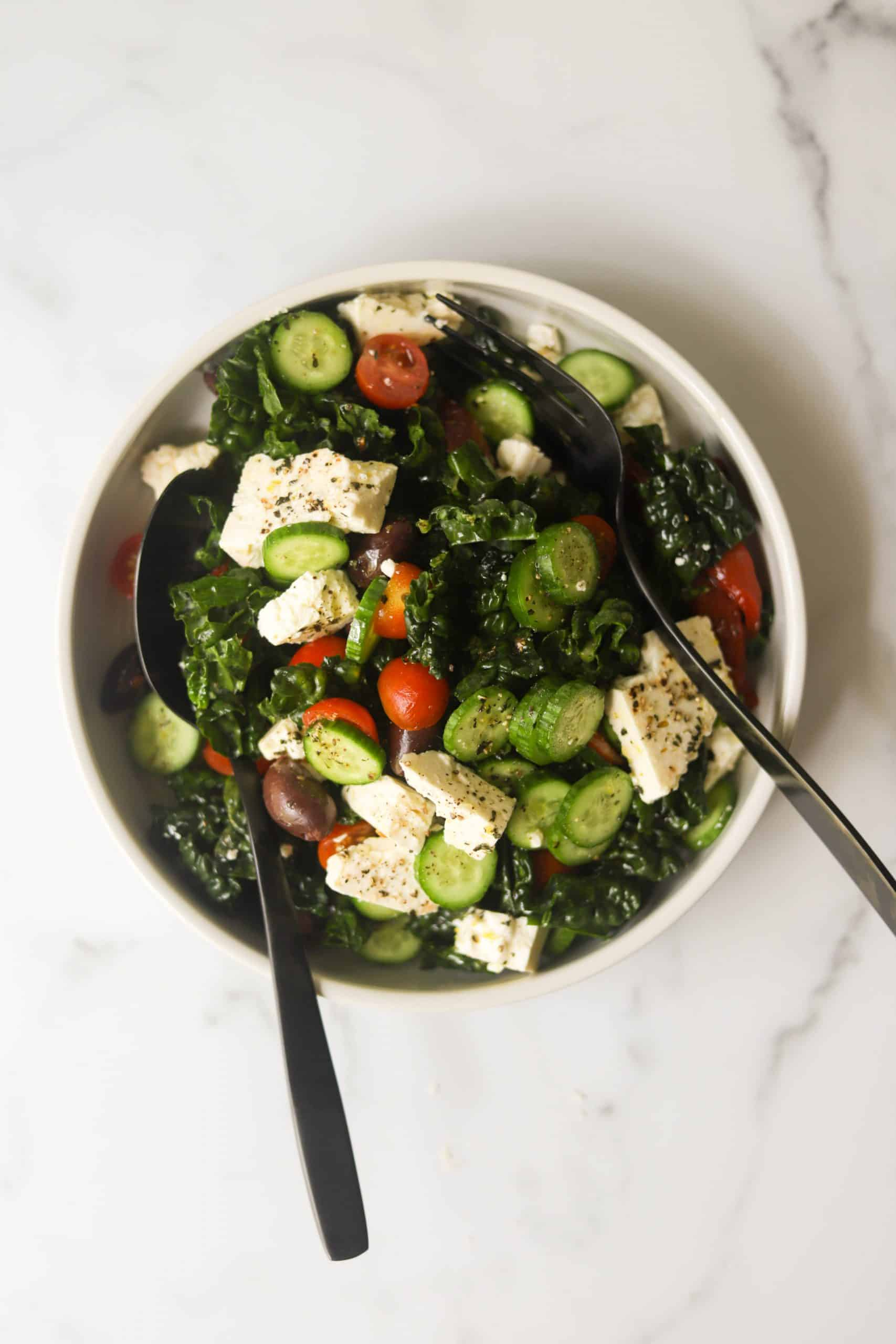 A bowl of Mediterranean kale salad with spoons.