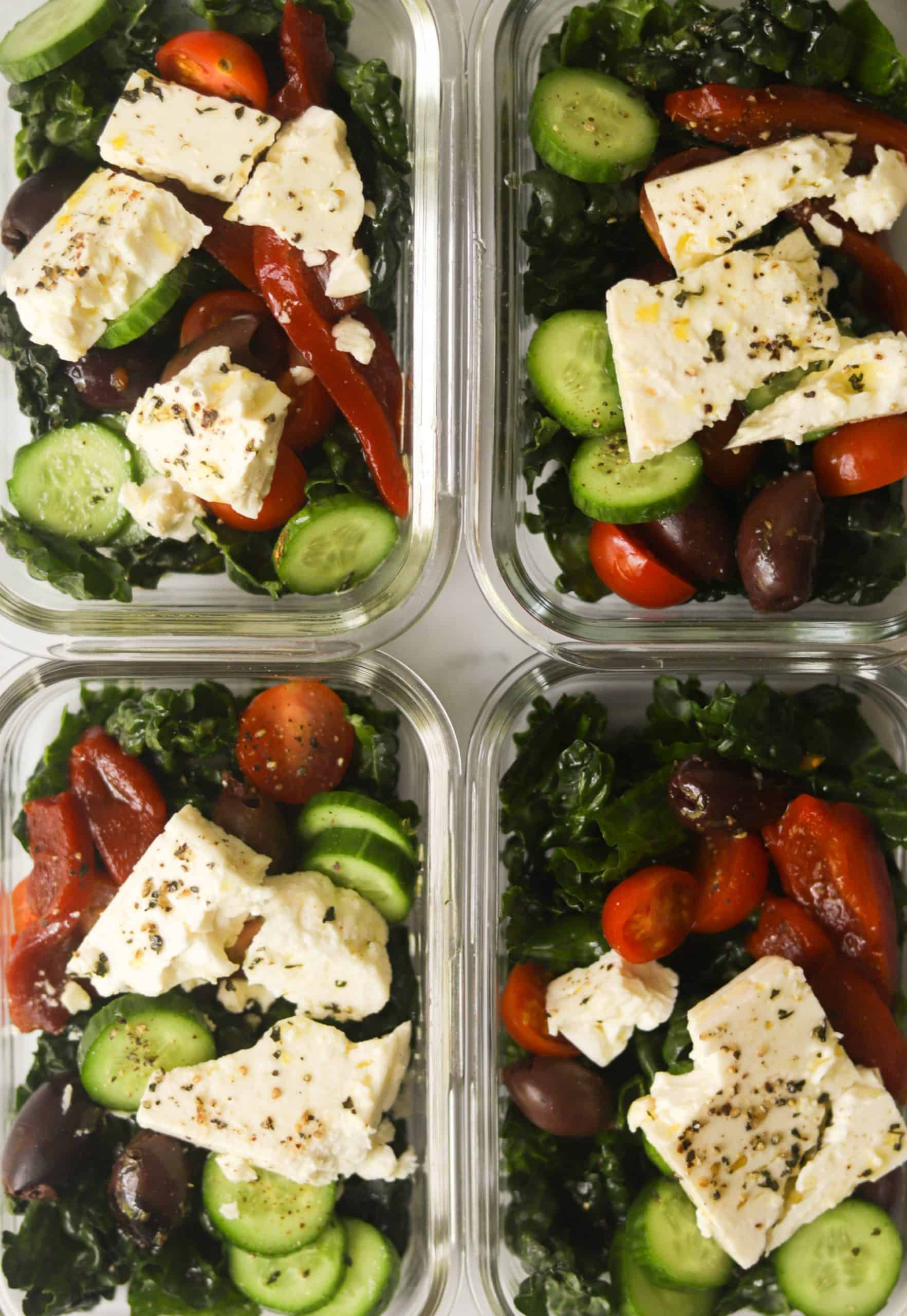 Meal prep containers with Mediterranean kale salad.