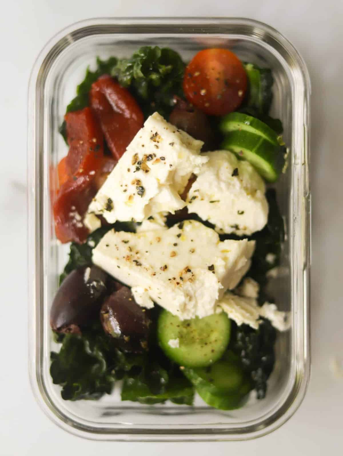A meal prep container with kale salad.