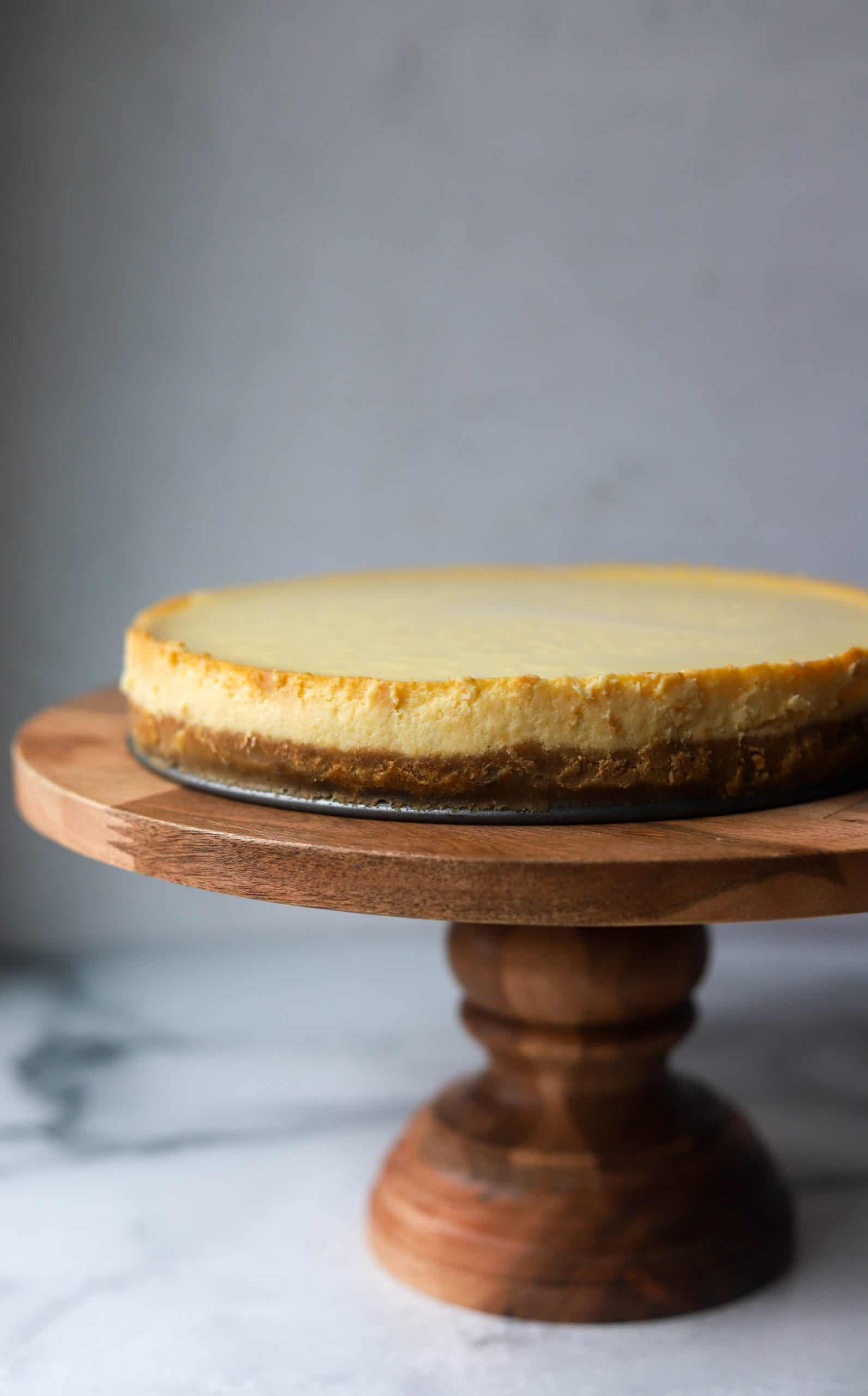 A whole cheesecake on a wooden cake stand.
