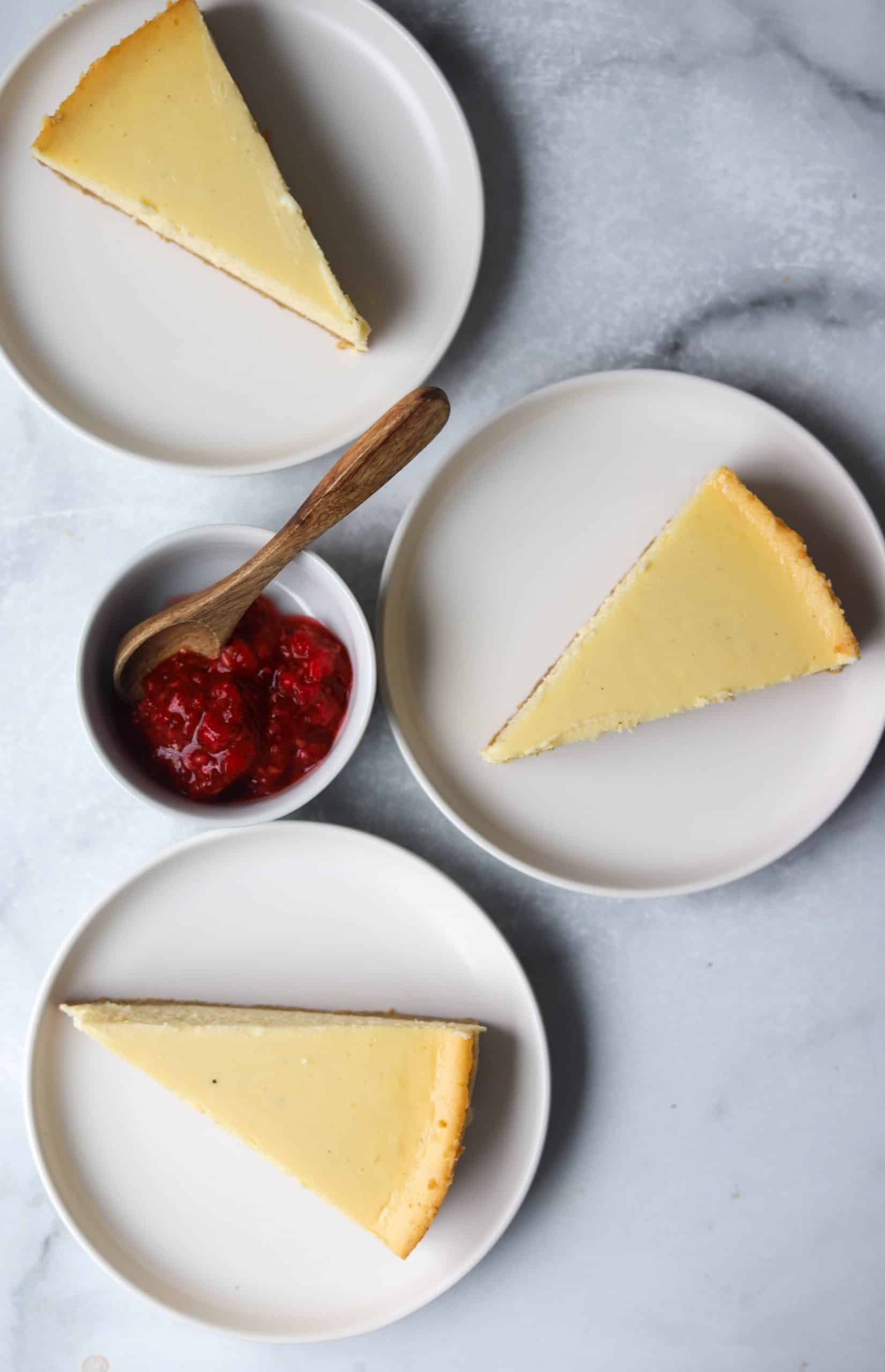 Slices of cheesecake on a plate with a small bowl of raspberries.
