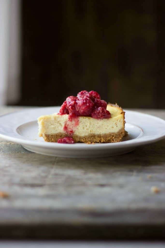 Italian ricotta cheesecake slice with berries on a white plate