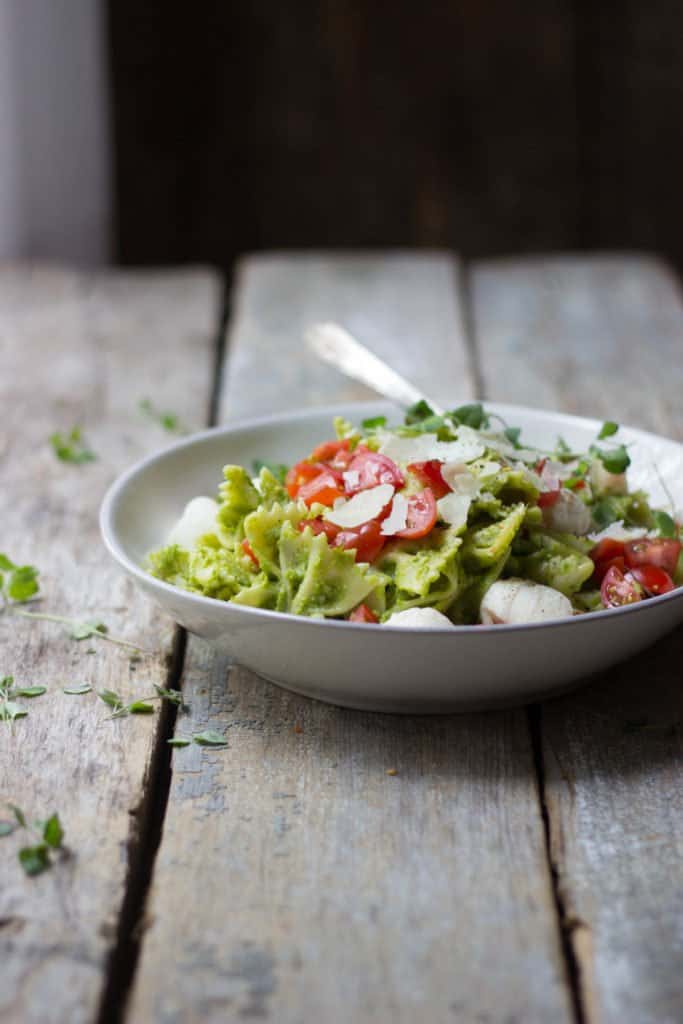 Caprese pasta salad with asparagus pesto in a white bowl