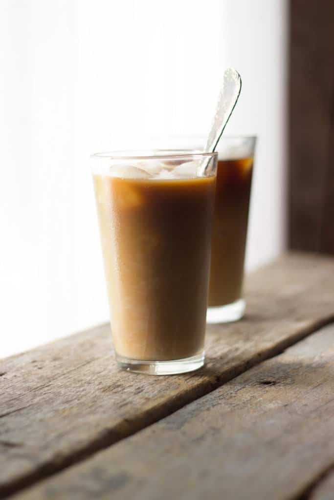 Side shot of Dulce de Leche Iced Americano in a glass cup with a spoon in it