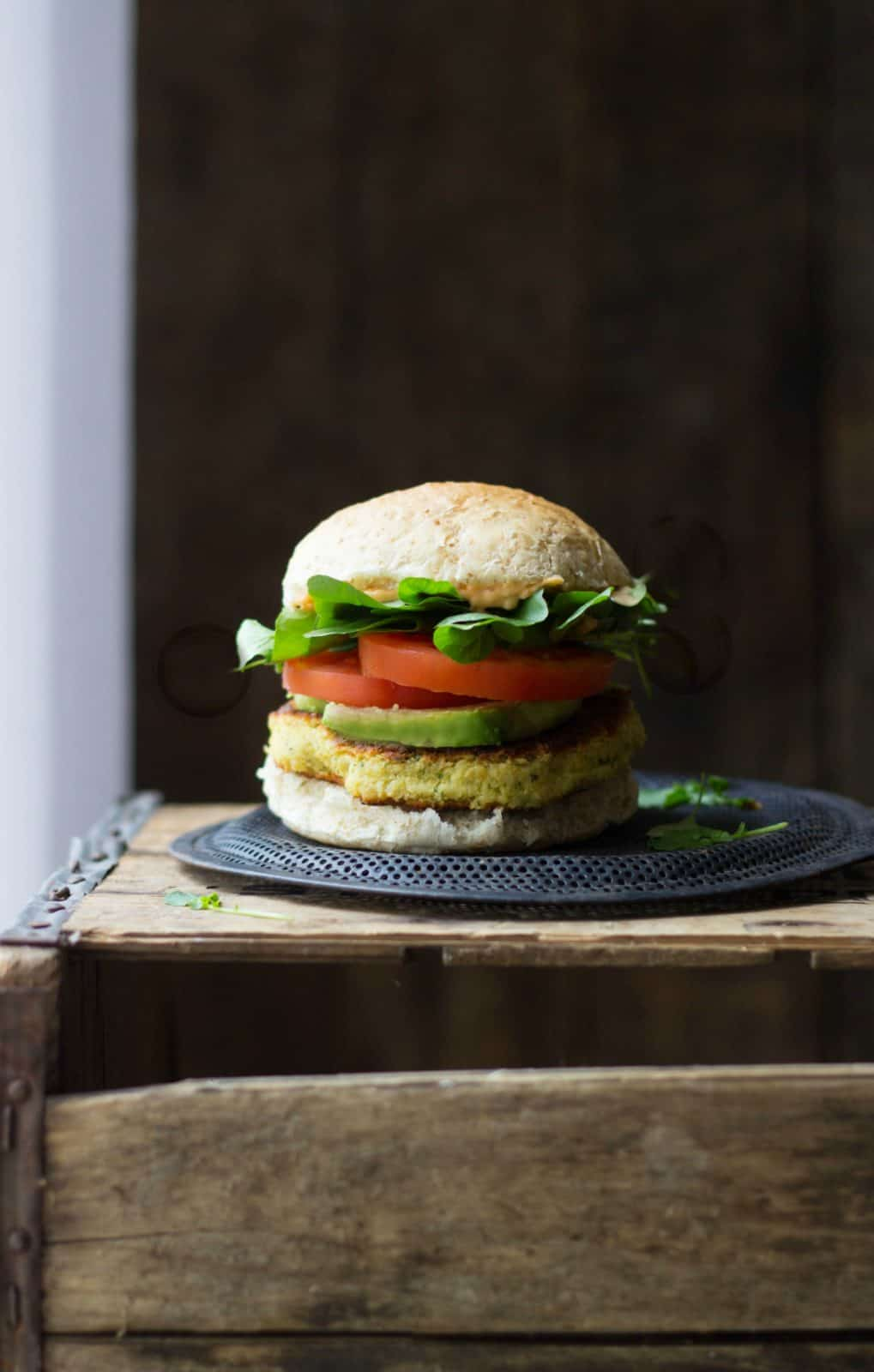 A side shot of a chickpea veggie burgers on a crate.