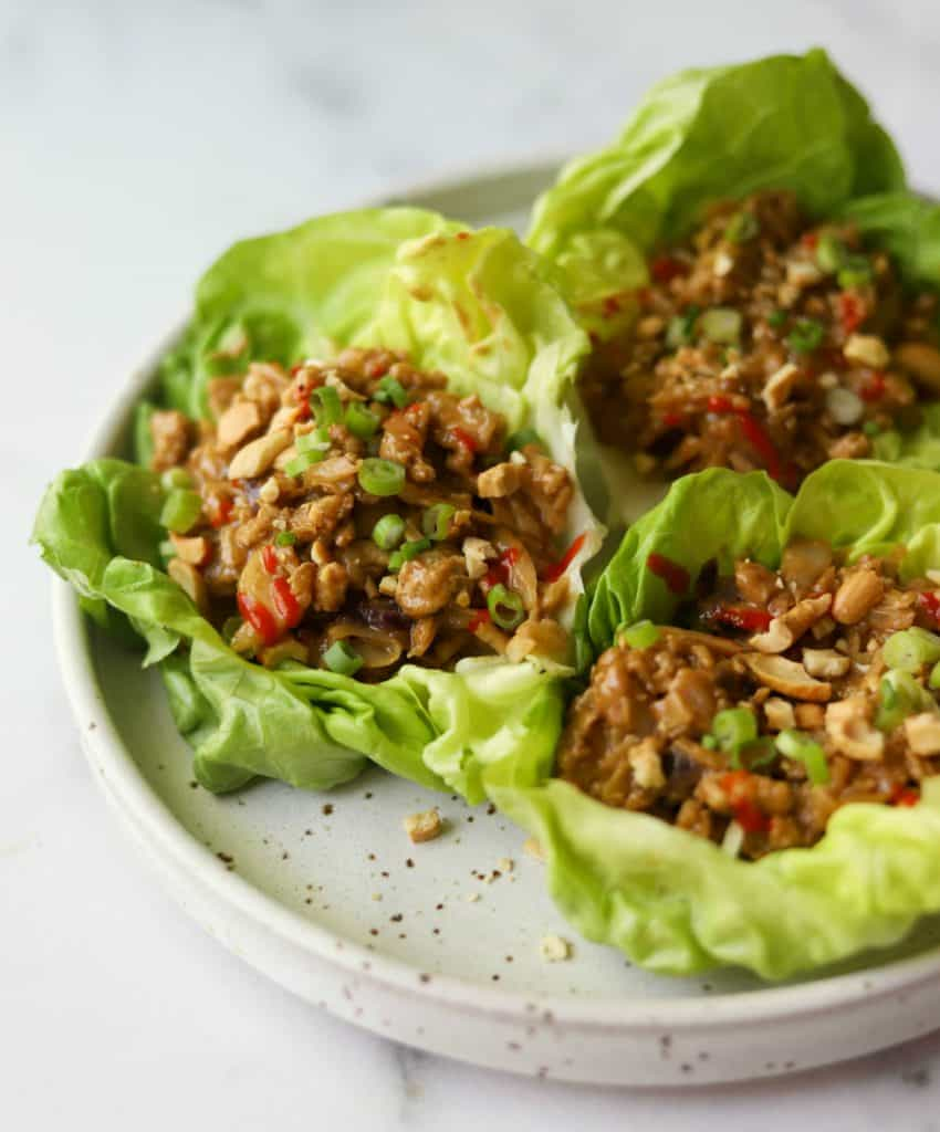 Cashew chicken lettuce wraps on a white speckled plate