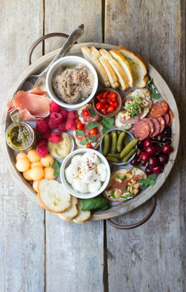 Overhead shot of charcuterie party board on a white round wooden dish.