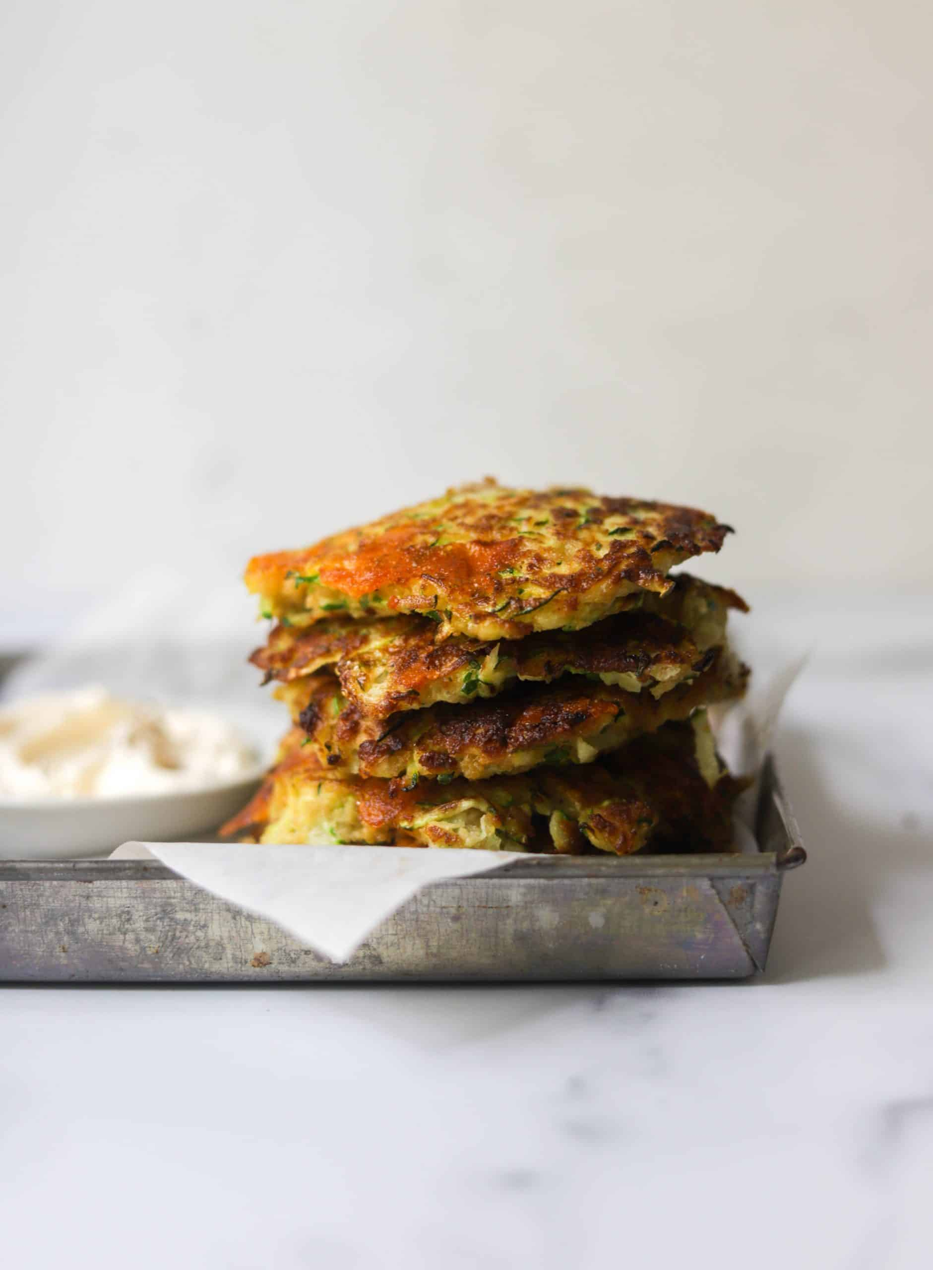 A stack of zucchini fritters on a tray.