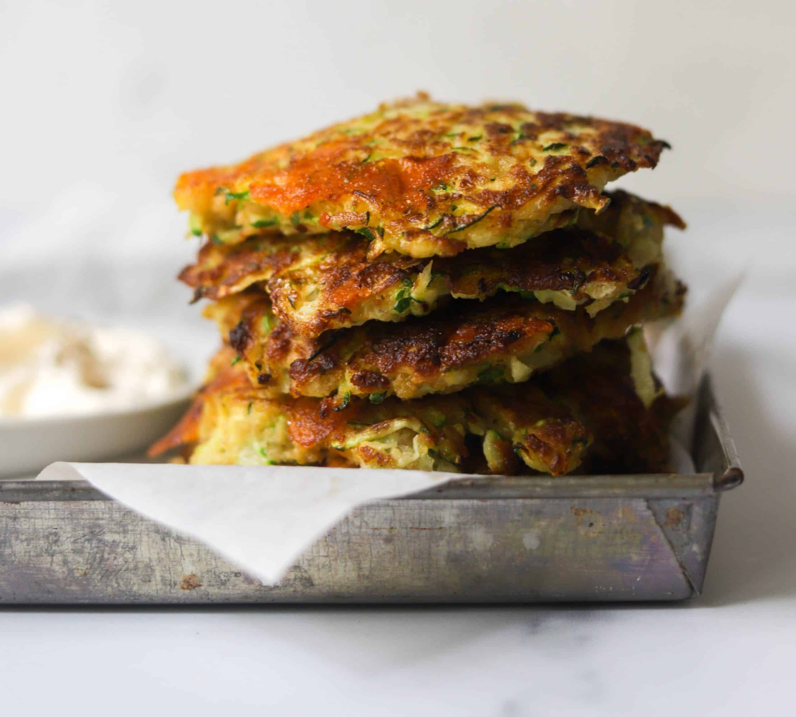 A stack of crispy zucchini fritters on a tray.