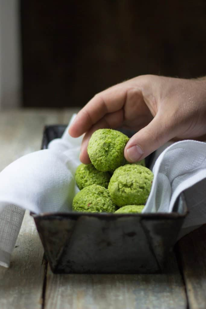 Edamame falafel in a tin with a hand picking one up.