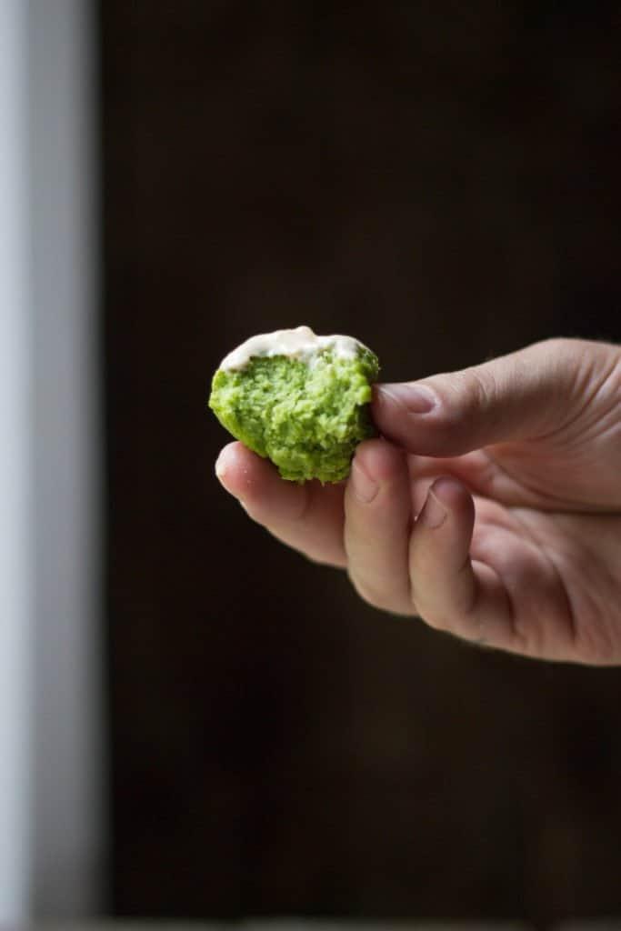 Hand holding one edamame falafel