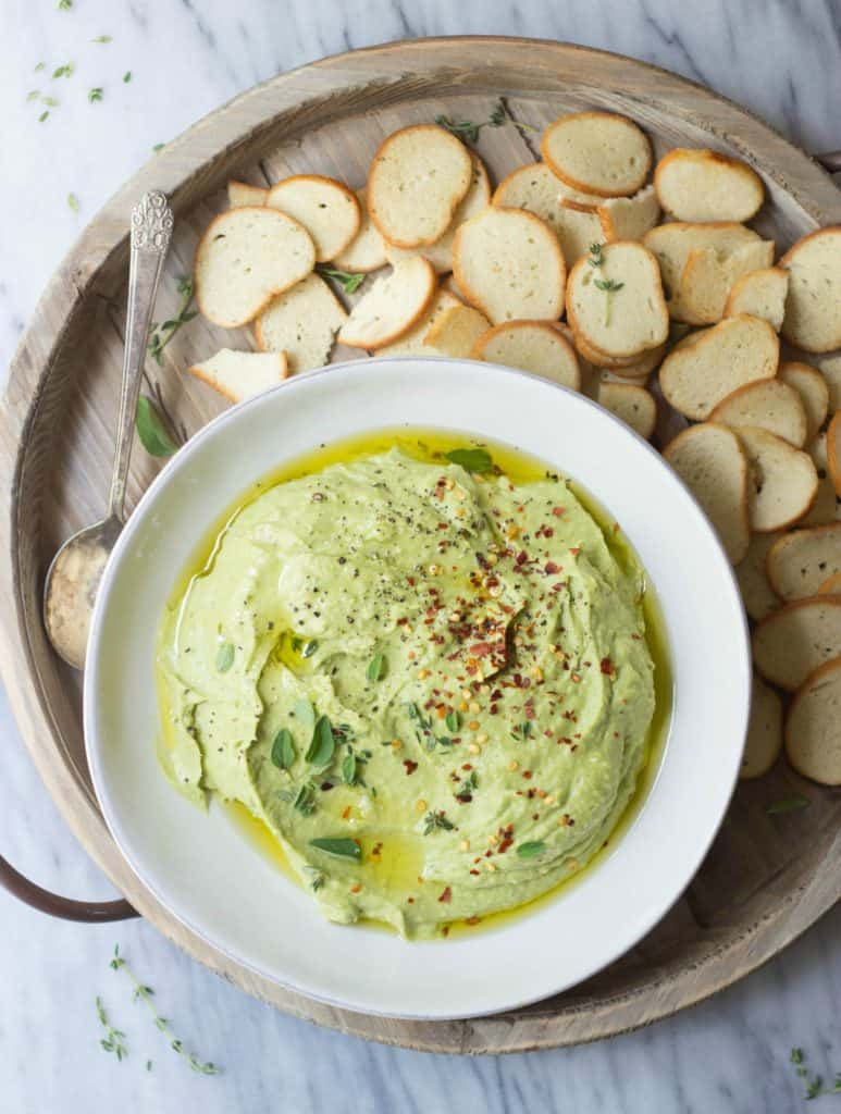 Whipped avocado white bean dip with bagel chips in a white bowl