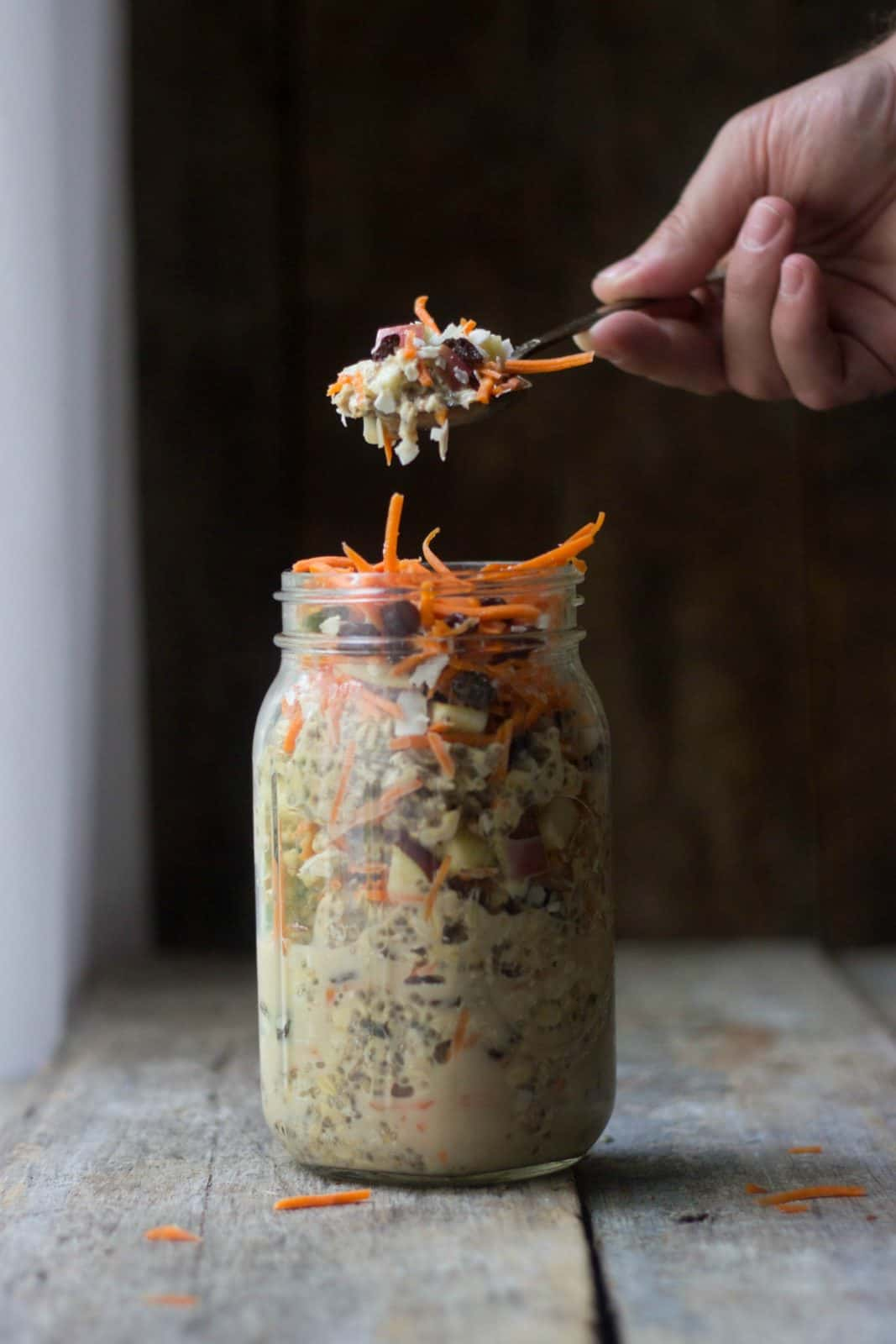 Overnight oats in a clear jar with a spoonful lifting out of it.