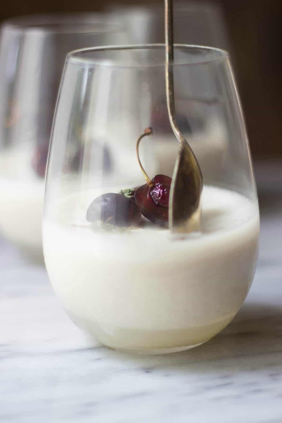 Close-up side shot of coconut milk panna cotta in a clear glass.