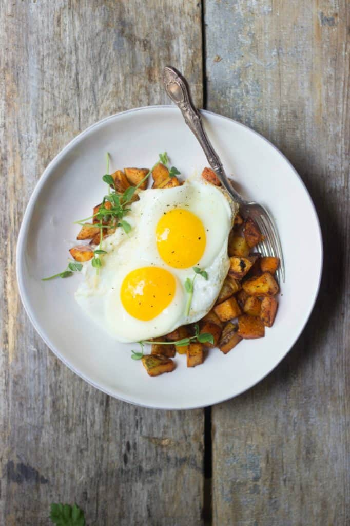 Crispy breakfast potatoes with fried eggs in a white bowl