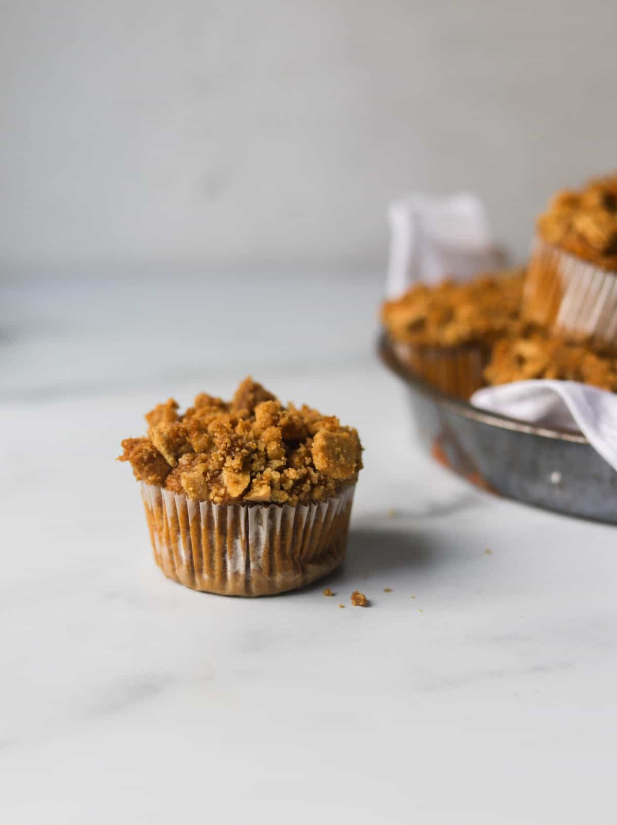 A side shot of a single muffin with a tin of muffins in the backdrop.