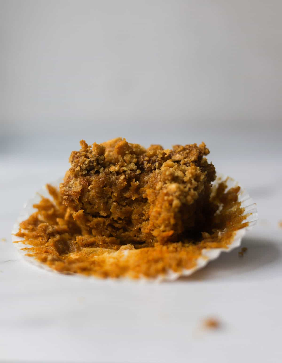 A side shot of a sweet potato muffin with a bite missing.