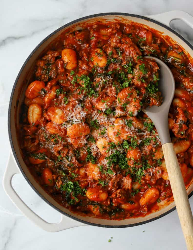 Italian Sausage, Kale & Gnocchi Skillet in a white pot as a simple weeknight dinner option to make cooking easier.