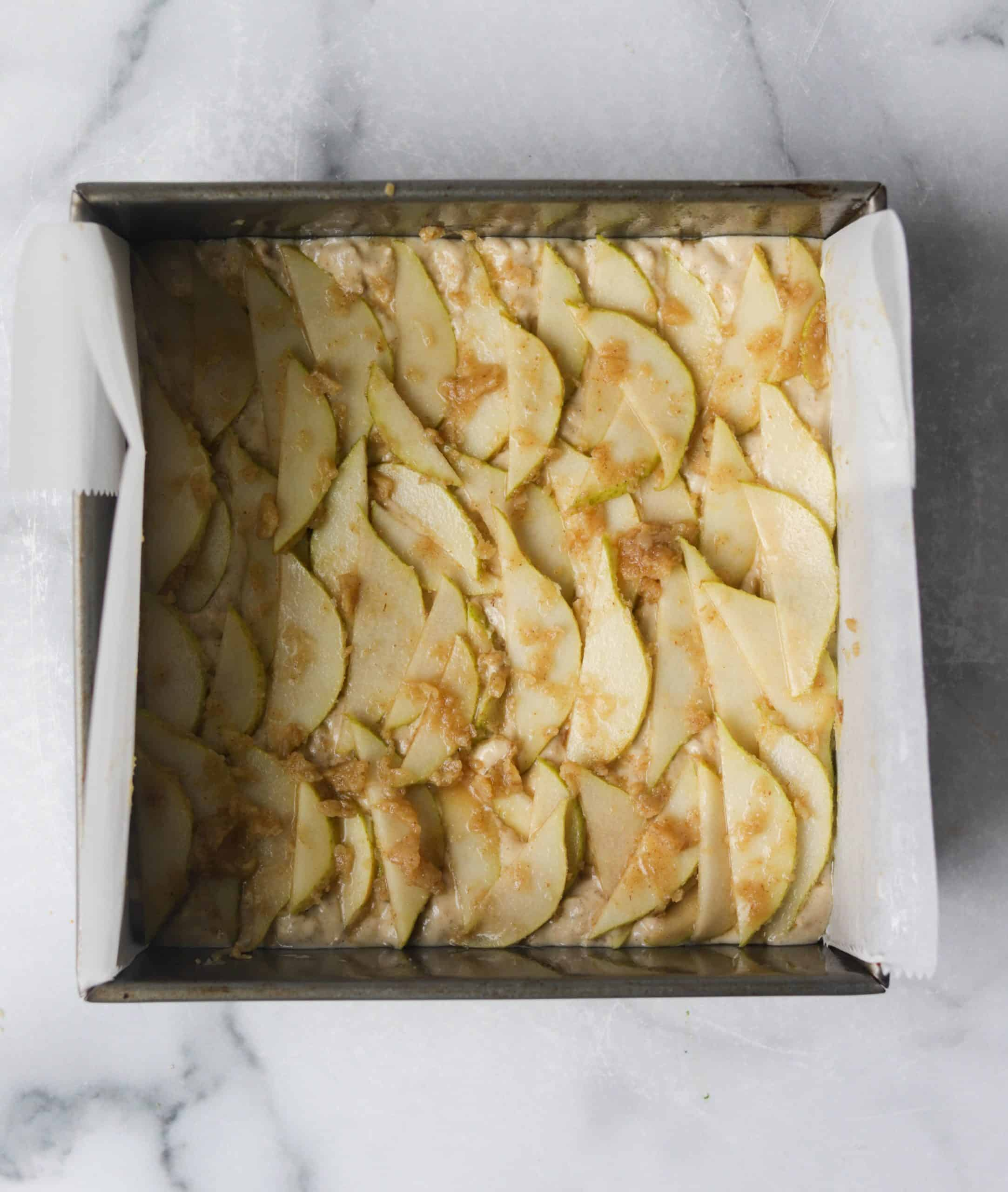 A cake pan filled with sliced glazed pears.