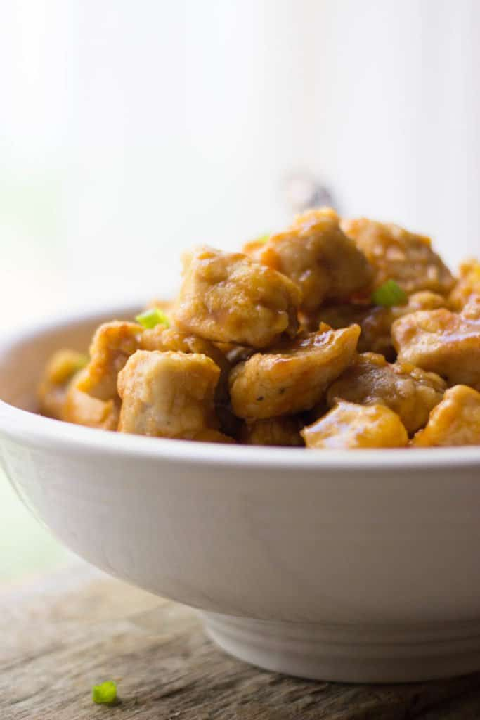 Side shot of finished sweet and sour chicken in a white bowl.