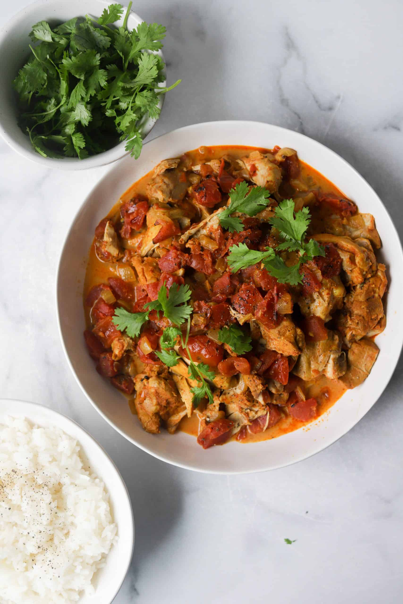 A large white bowl filled with chicken vindaloo and a side bowl of Jasmine rice and cilantro.