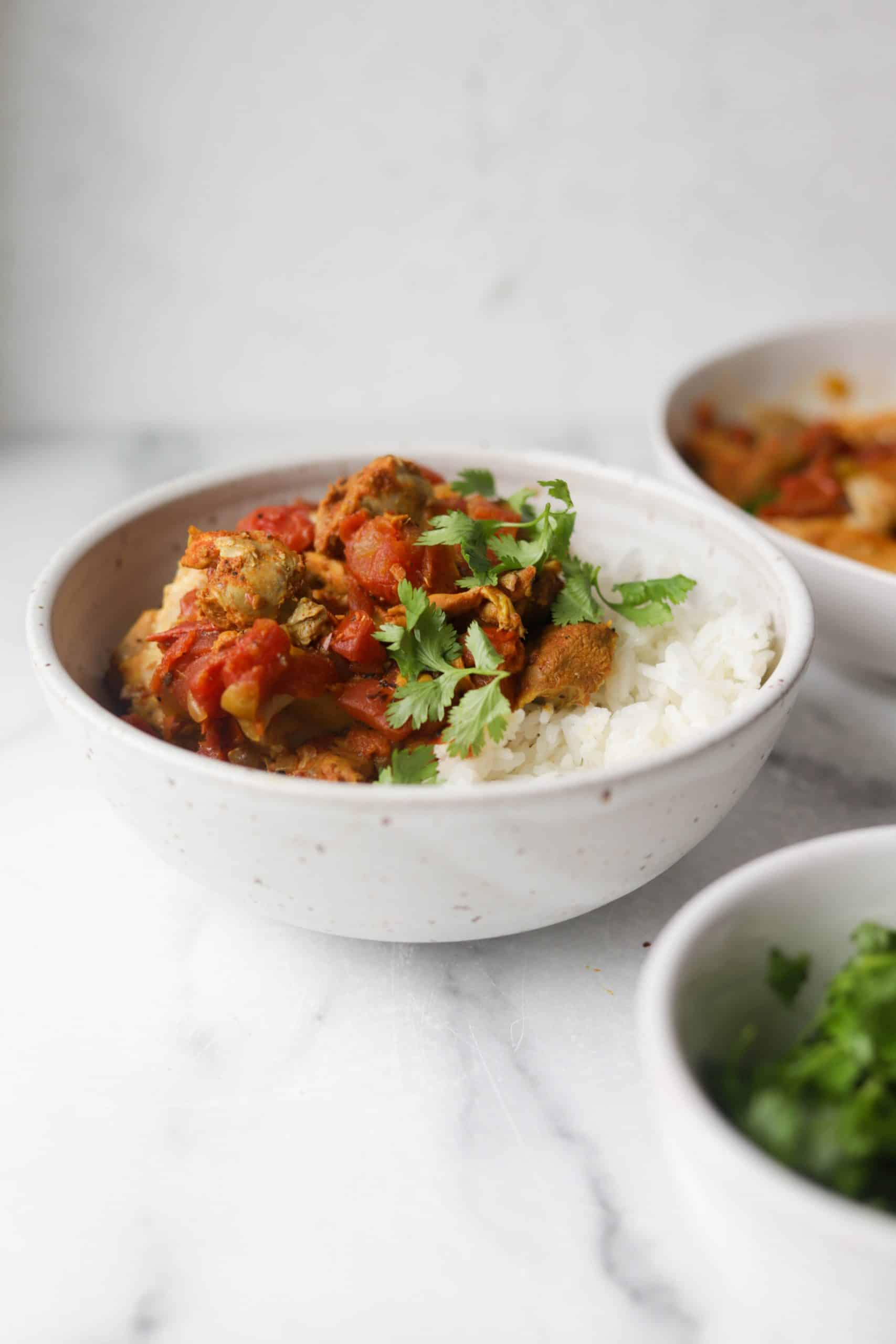 A white bowl with vindaloo chicken, Jasmine rice and cilantro.