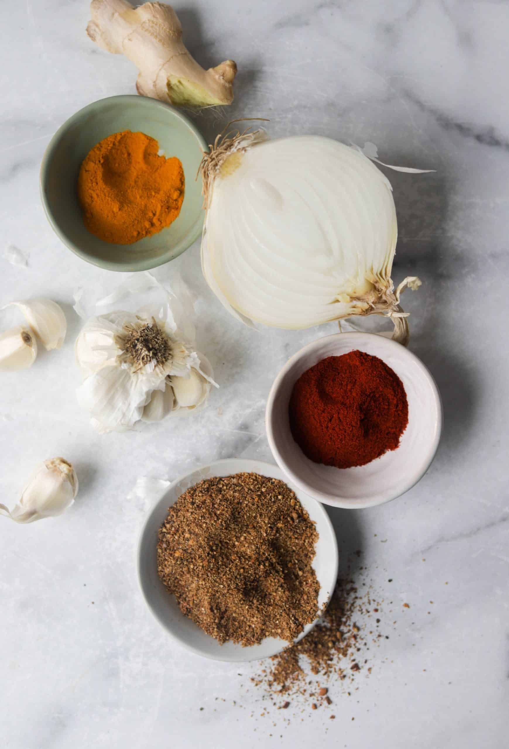 A white marble backdrop with onion, ginger, garlic and spices in bowls.