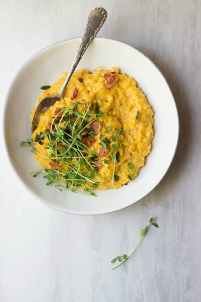 Overhead shot of risotto made with butternut squash and bacon in a white bowl and topped with microgreens.