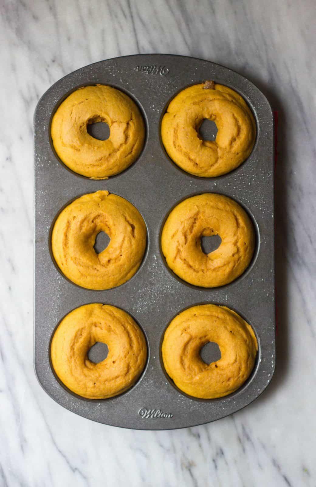 Overhead shot of baked cinnamon sugar pumpkin donuts sitting in a dark grey donut pan.