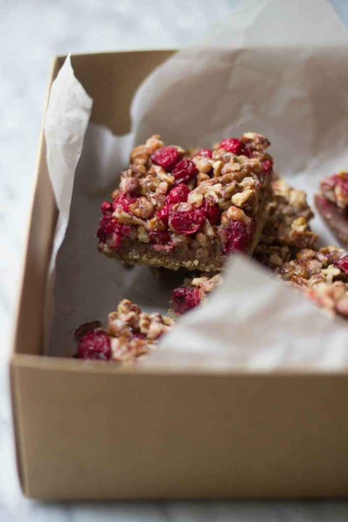 Angle shot of cranberry pecan bars in a container with white parchment paper.