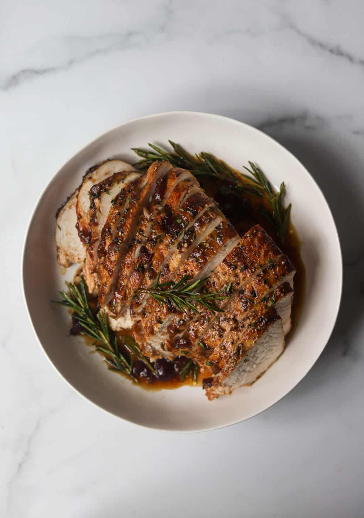 An overhead shot of a seared turkey breast with cranberry orange glaze and rosemary sprigs in a white bowl.