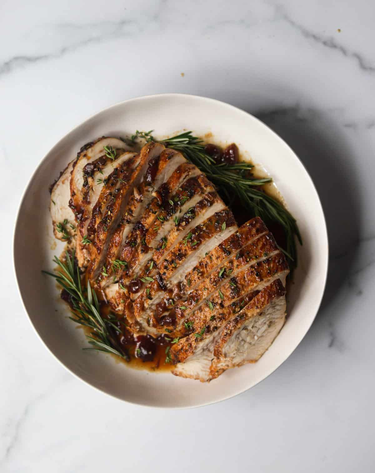 An overhead shot of dutch oven turkey breast on a platter with herbs and cranberries.