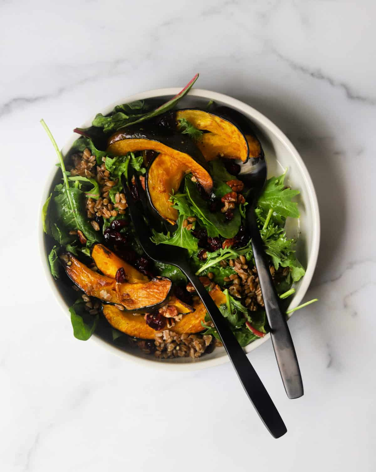 An overhead shot of a bowl of roasted acorn squash salad with two black serving utensils.