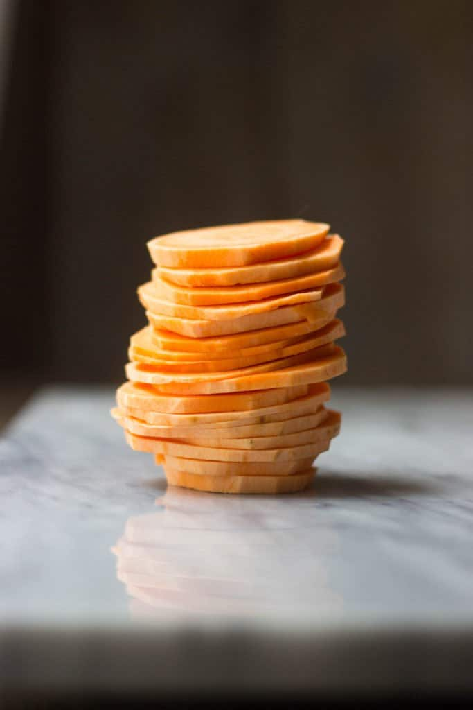 A stack of round, thinly sliced sweet potatoes prior to being cooked.