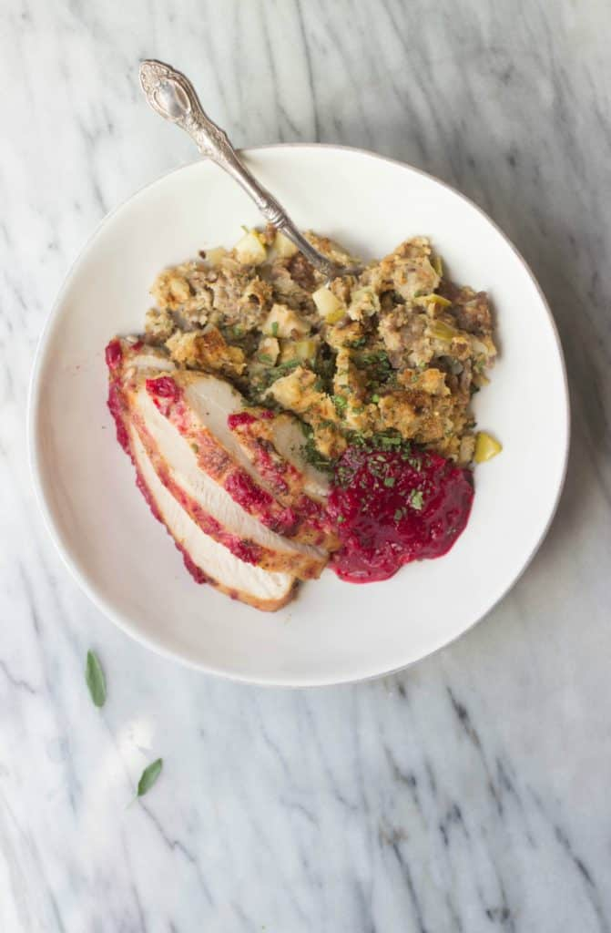 Overhead shot of finished recipe for Cranberry-Orange Glazed Turkey Breast + Apple Sausage Stuffing on a white plate.