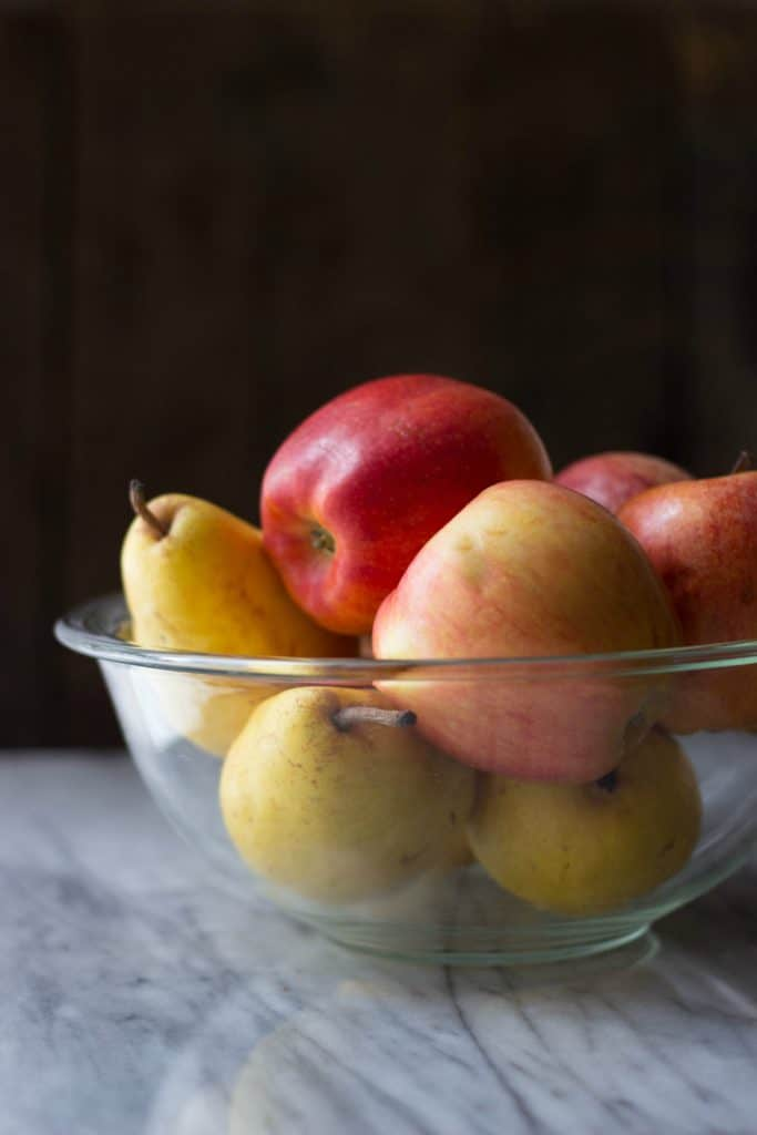 Side shot of whole fresh apples and pears in a glass bowl.