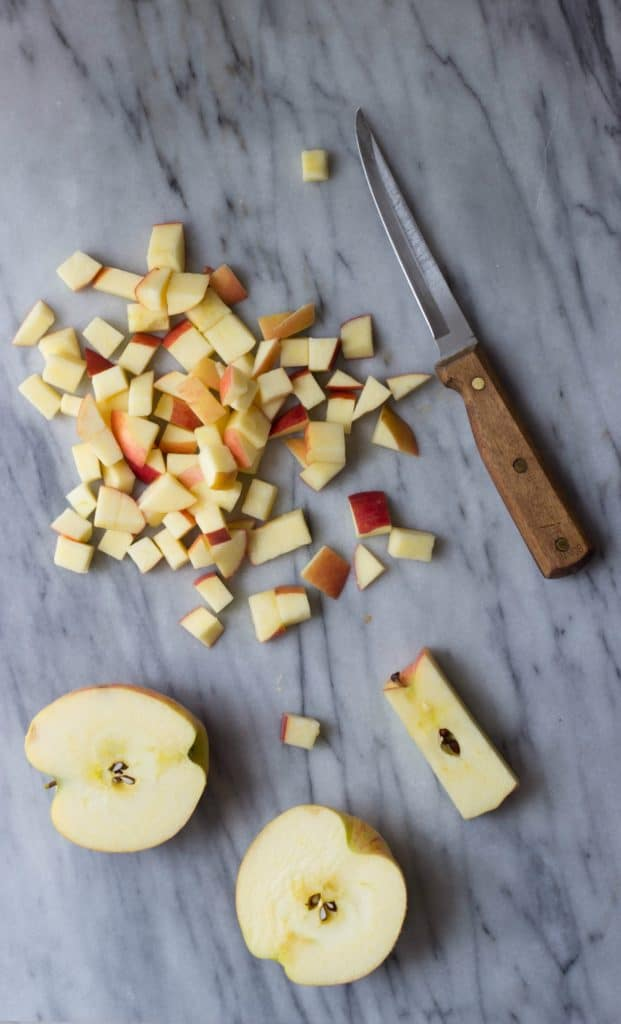 Overhead shot of apples diced on a white marble background with a knife.
