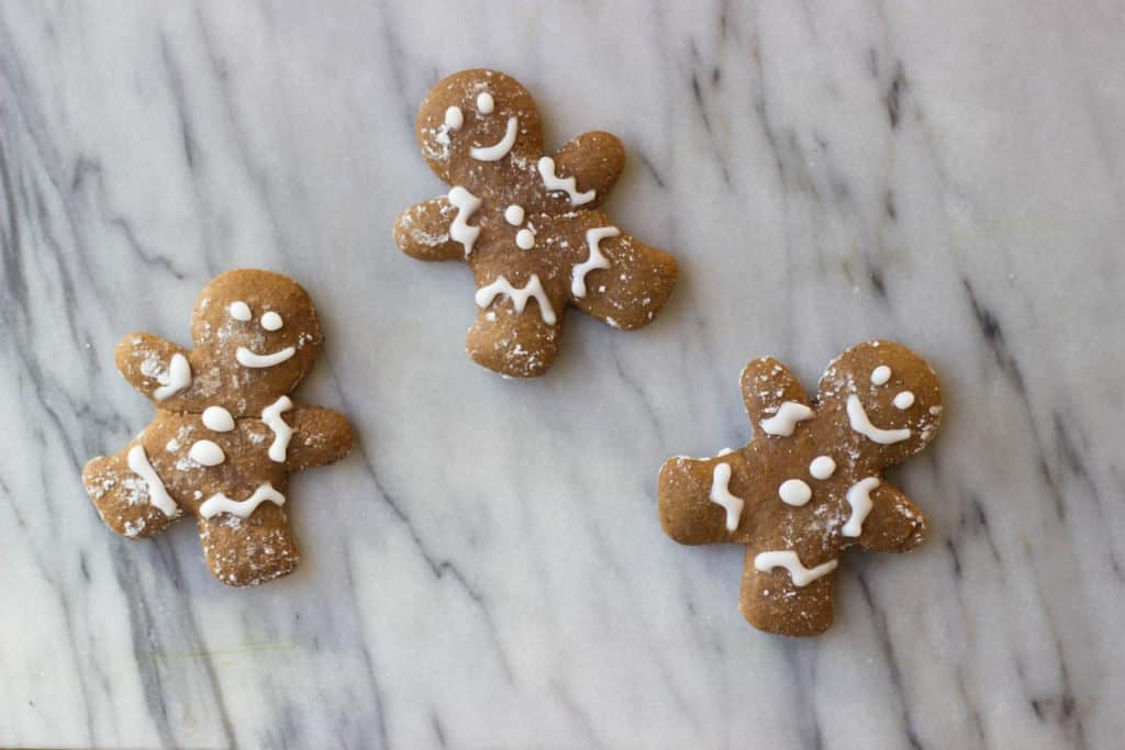 Overhead shot of three Gingerbread Cut-Out Cookies decorated with white icing.
