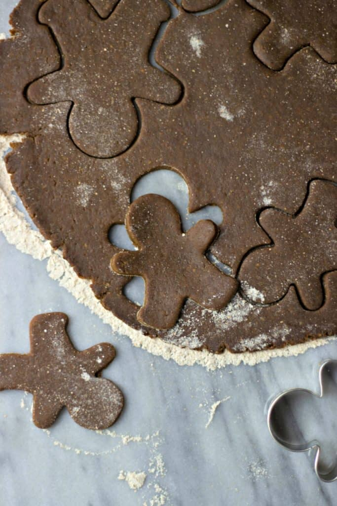 Overhead shot of gingerbread man cut-out from flat dough.