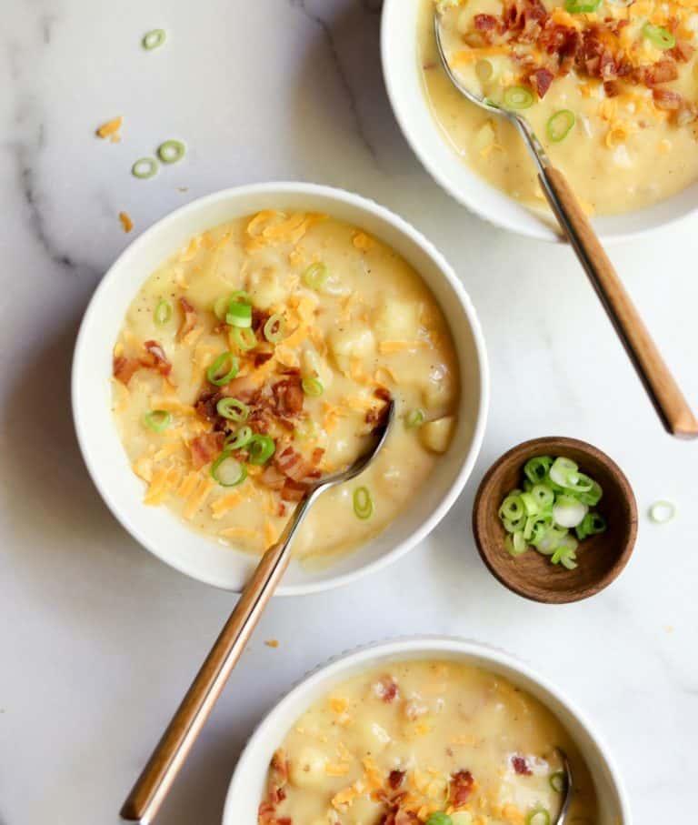 Cheesy potato soup in white bowls
