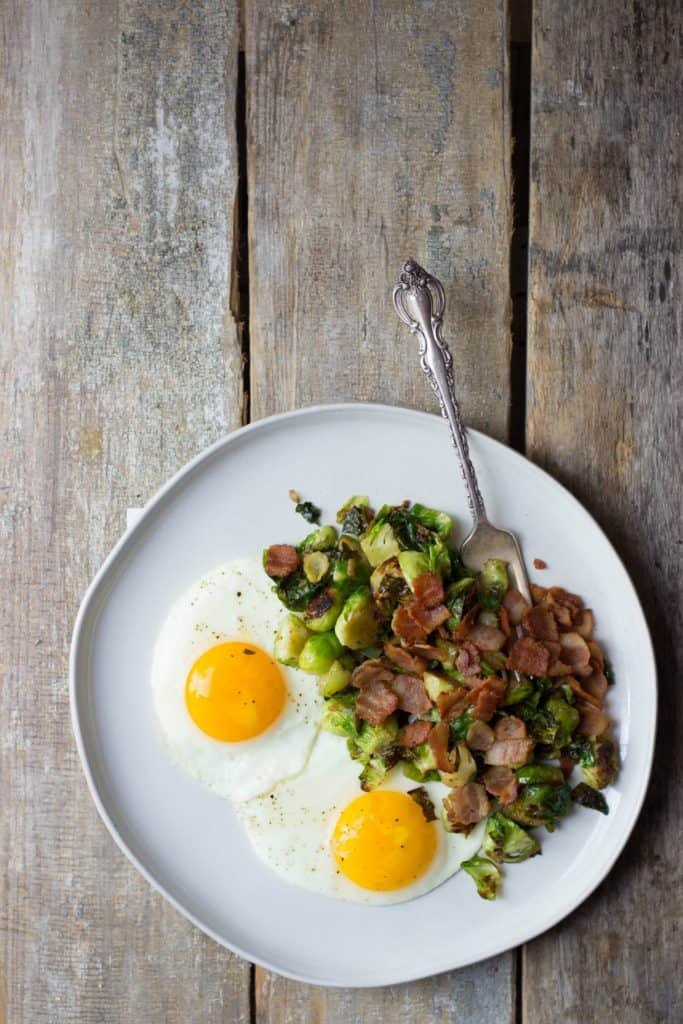 Overhead shot of finished Breakfast Brussels Sprouts recipe on a white plate.