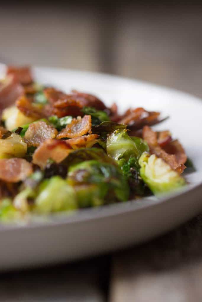 Side shot focused in on the cooked bacon on top of finished Brussels sprouts in a white plate.