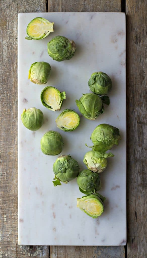 Raw Brussels sprouts on a marble slab with some cut into halves.