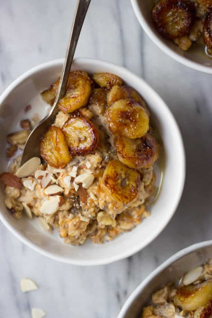 Overhead shot of caramelized banana & peanut butter oatmeal in a white bowl.
