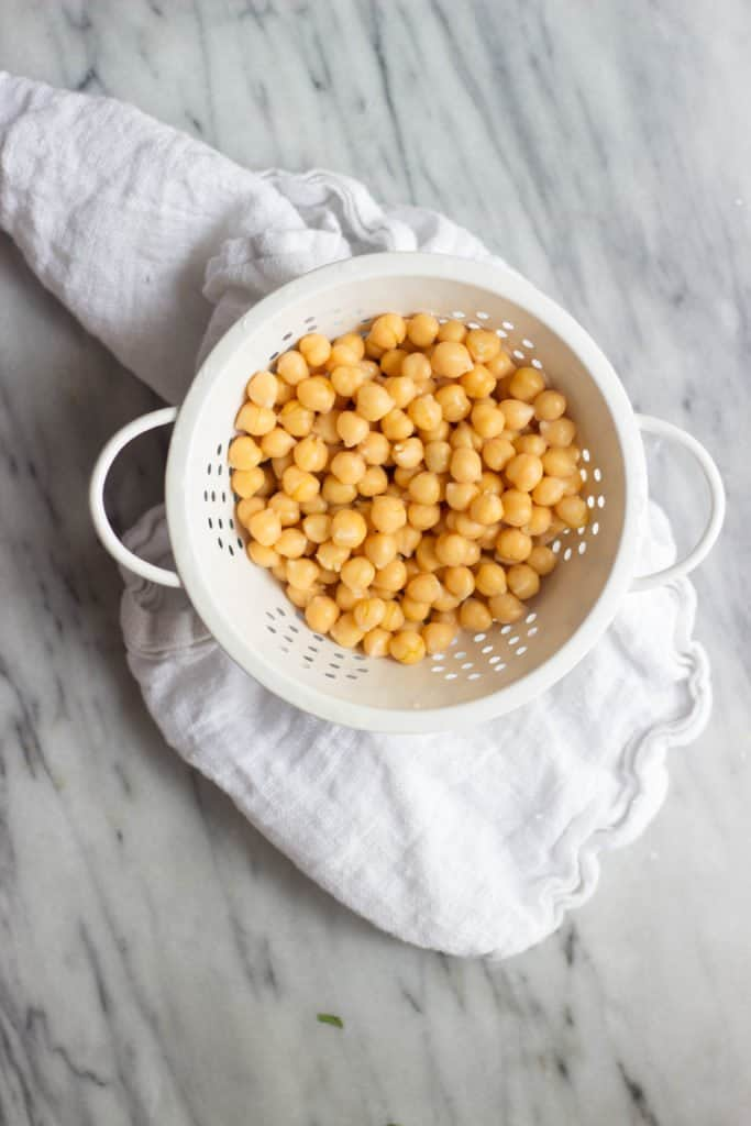Overhead shot of chickpeas in a white colander.