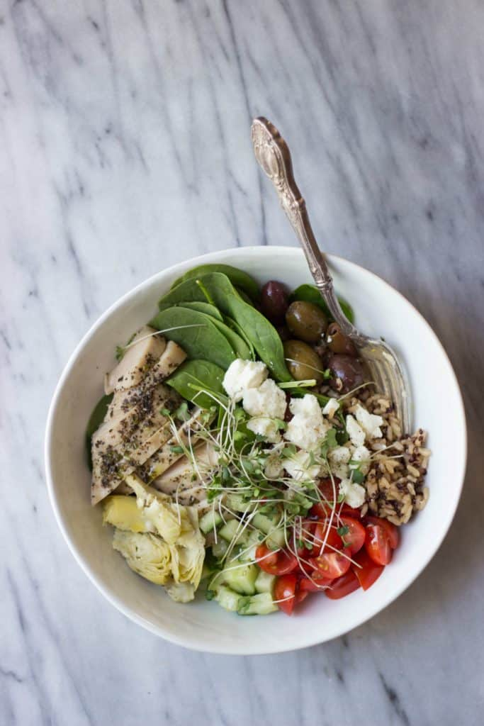 Overhead shot of greek chicken bowls in a white bowl