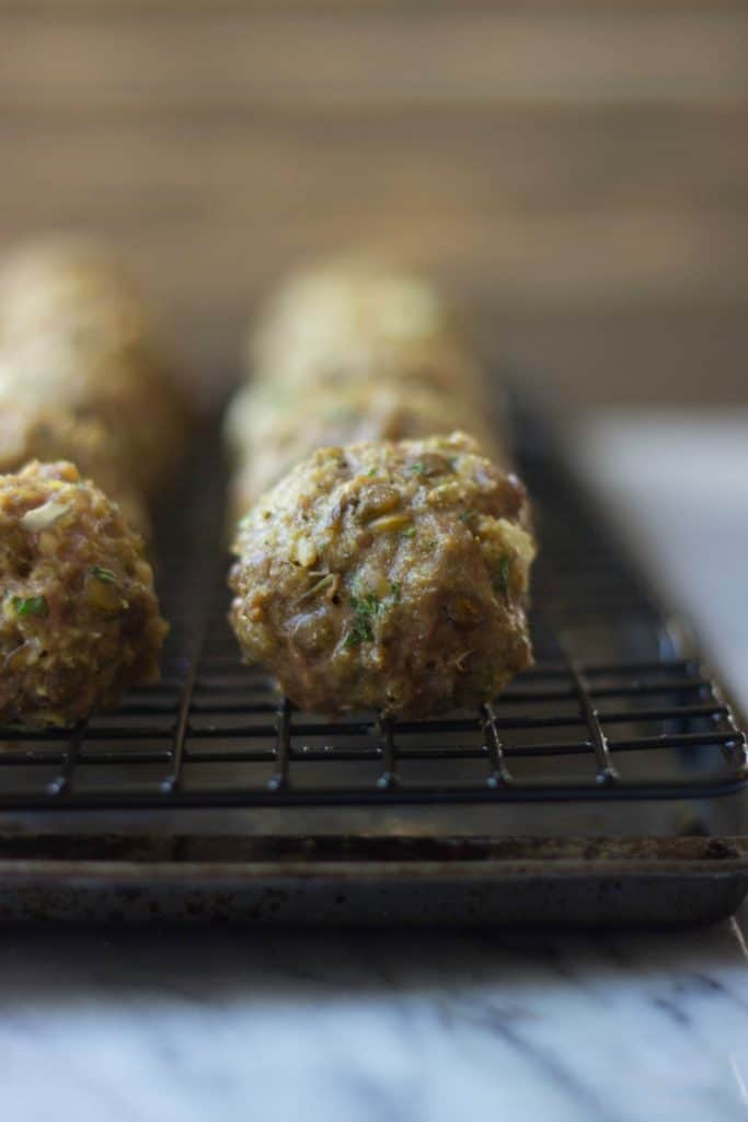 Cooked lamb lentil meatballs on a wire rack in a sheet pan.