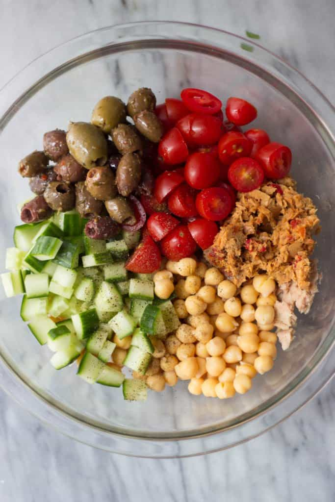 Overhead shot of all ingredients for Mediterranean Chickpea & Tuna Salad - fresh tomatoes, cucumber, olives, chickpeas and tuna.