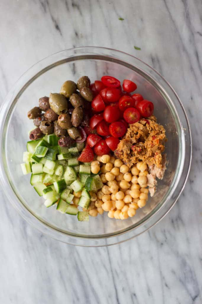 Overhead shot of Mediterranean Chickpea & Tuna Salad ingredients in a clear bowl.