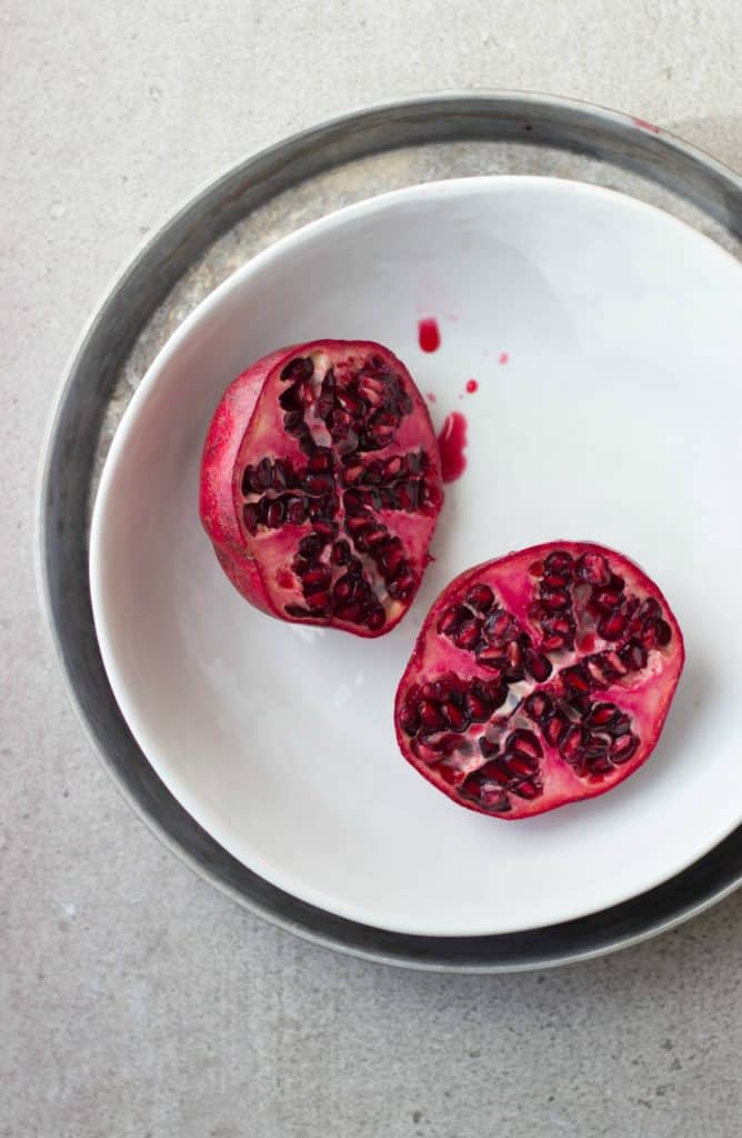 Overhead shot of one pomegranate cup open in a white bowl.